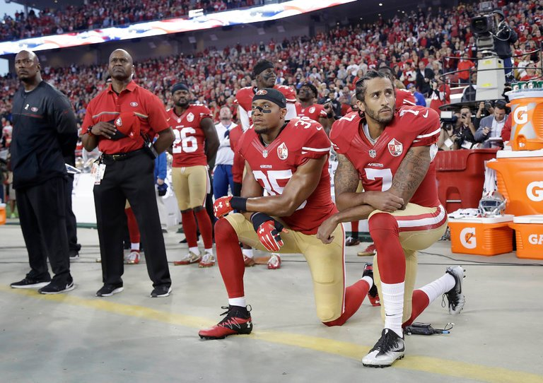 Colin Kaepernick (right) and Eric Reid (left) taking action during a football game by kneeling during the National Anthem.