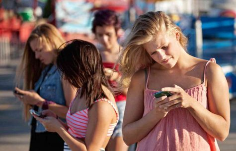 google images  Shown here is the common sight of teenagers addicted to their phones, probably checking Snapchat.