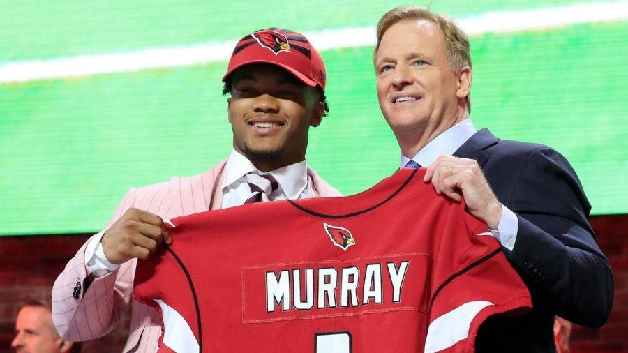 Kyler+Murray%2C+the+first+overall+pick+in+the+2019+NFL+draft%2C+holds+his+new+Arizona+Cardinals.+